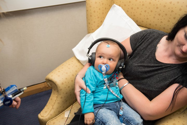 A little baby with a dummy in is wearing headphones while sitting on his mothers lap