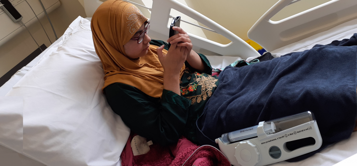 young patient in headscarf reading their phone while having an immunology infusion on a hospital bed