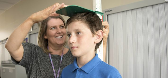 School nurse measures child