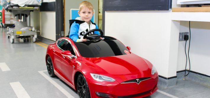 Child drives a mini Tesla car