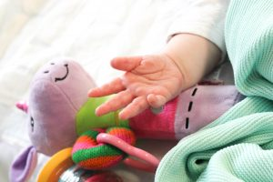 A baby's hand touching their purple teddy