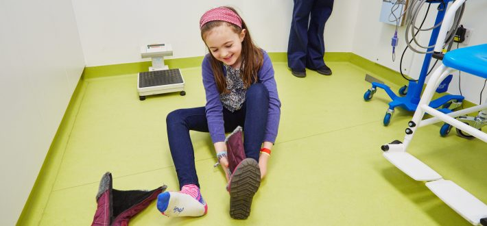 A smiling girl puts her shoes on