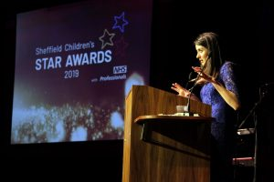 Amy Garcia presents from the podium at the 2019 Star Awards