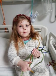 Young girl in hospital bed playing with tinsel