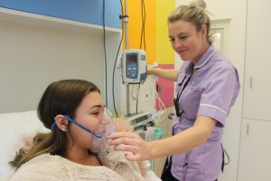 Lucy Mountain getting help from a nurse with her oxygen mask at Sheffield Childrens Hospital