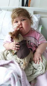 Young girl in hospital bed with toy recovering from leukaemia