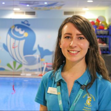 Picture of a therapy assistant by a brightly decorate hydrotherapy pool