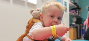 Young boy showing his bright yellow eyeband wristband