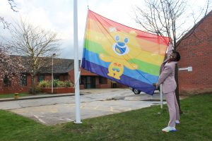 Dr Ronx raising the Rainbow Flag