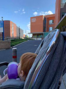 Child outside hospital in pram