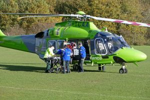 People taking a stretcher into a helicopter