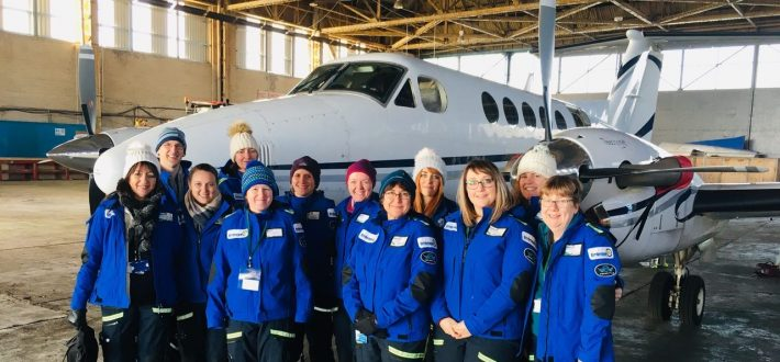 Group of medical professionals stood in front of small plane