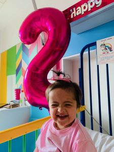 Amarah, two, smiling with a pink top next to a big pink number 2 balloon