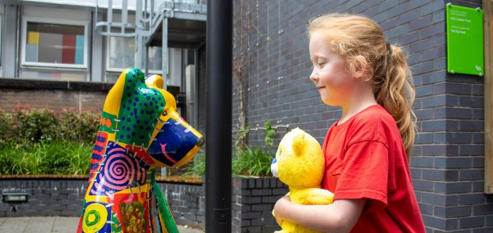 bears of sheffield painted bear statue stood next to young girl, ginger hair with red top holding a yellow theo bear