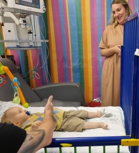 baby Edward laid in a cot with dad next to him and mum looking down smiling