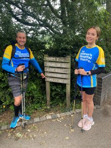 Molly wearing The Childrens Hospital Charity blue and yellow tshirt next to a sign for the Tissington Trail with hiking poles and trainers