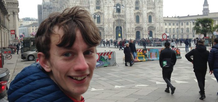 Dan, white with brown hair caught by the wind, smiling and looking at the camera with a blue coat, in the background is a historic building