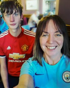Dan in a red football shirt with his mum in a blue football shirt. its a selfie, both smiling with brown hair